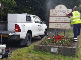 Jet washing a sign in Bideford