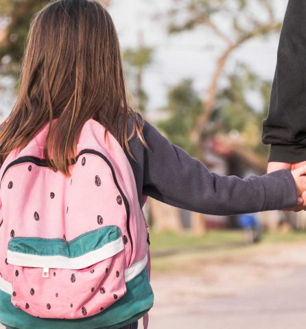 young girl holding a mans hand facing away
