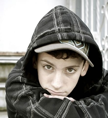 photo of a teenage boy wearing a hoody with his arms crossed