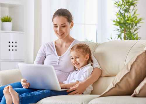 mum with young girl sat on sofa smiling, with a laptop