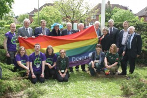 DCC Staff holding up a rainbow flag smiling