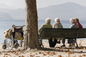 older people sat on a bench on a bright sunny day looking at lovely view