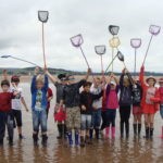 a group of children holding fishing nets in the air