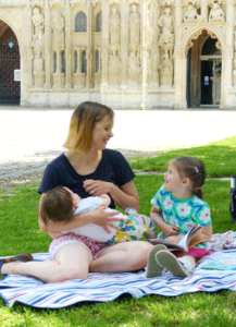 Mother breastfeeding in public with an older child sitting next to her