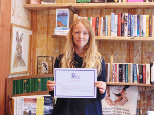 Kayleigh Diggle of Liznojan Books in Tiverton is the first business to sign up to the scheme, pictured holding her certificate