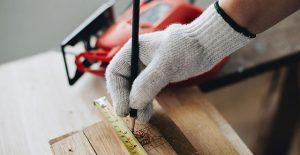 A tradesman measuring some wood